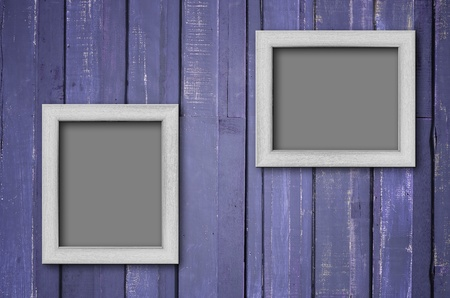 Two white wood picture frame on Purple color paint plank wall for background Standard-Bild