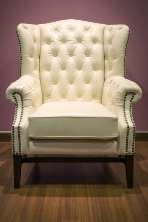 chesterfield: Front of Classic Chesterfield luxury White Leather armchair on Wood floor