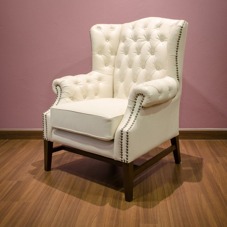 Side of Classic Chesterfield luxury White Leather armchair on Wood floor photo