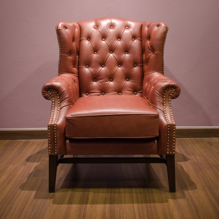Front of Classic Chesterfield luxury Brown Leather armchair on Wood floor photo
