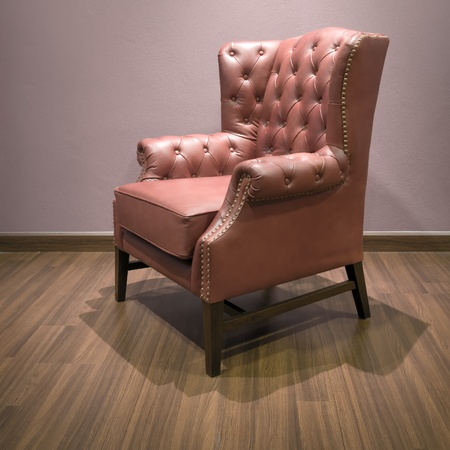 Side of Classic Chesterfield luxury Brown Leather armchair on Wood floor photo
