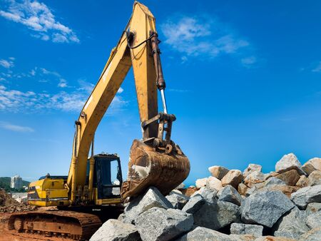 Yellow tracked excavator working on a large pile of rock Stock Photo - 13714421