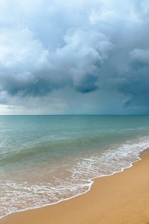 Storm cloud the sea and white wave on sandy beach photo