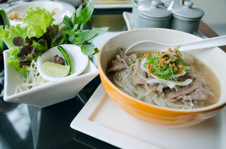 lao: Pho Lao style noodle soup with vegetables on table