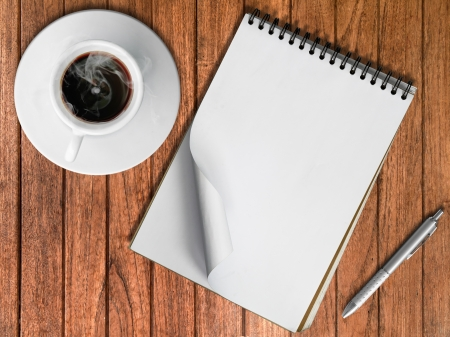 Sketch book Silver pen and White cup of hot coffee on wood table photo
