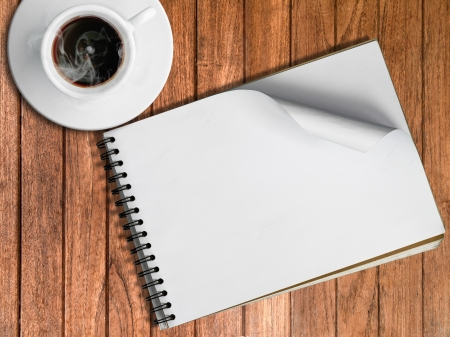 Sketch book and White cup of hot coffee on wood table photo