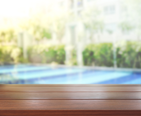 swimming pool: Wood Table Top Of Background And Pool