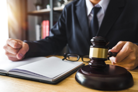 Justice and law concept.Male judge in a courtroom with the gavel,working with,digital tablet computer docking keyboard, eyeglasses,on wood table