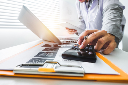 Healthcare costs and fees concept.Hand of smart doctor used a calculator and tablet for medical costs at modern hospital in sun light Stock Photo