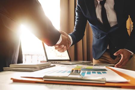 Deux homme d'affaires confiant se serrant la main lors d'une réunion au bureau, succès, traitement, salutation et partenaire à la lumière du soleil