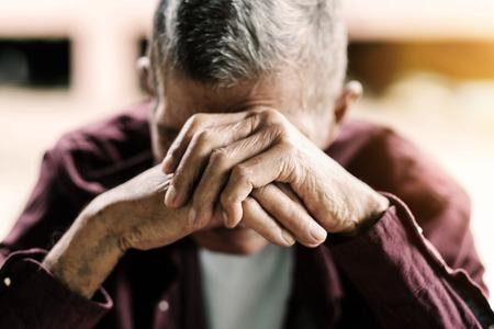 Hombre mayor que cubre su rostro con sus manos tono vintage. Foto de archivo