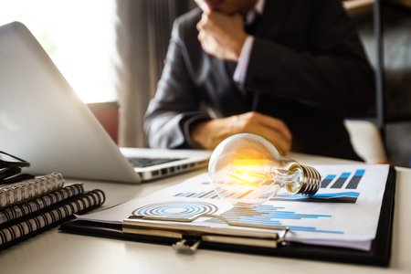 Bombilla con mano de negocios trabajando con computadora portátil y estrategia comercial creativa en la luz de la mañana