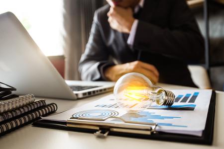 Glühbirne mit Geschäftshand, die mit Laptop-Computer und kreativer Geschäftsstrategie im Morgenlicht arbeitet