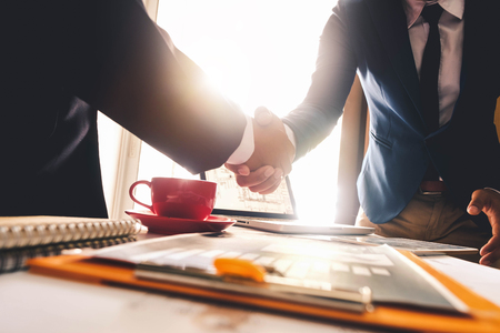 Due uomini d'affari fiduciosi che agitano le mani durante una riunione in ufficio, successo, trattare, saluto e partner alla luce del sole