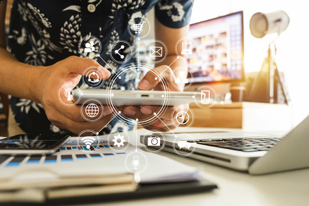 Man using smart phone for mobile payments online shopping,omni channel,sitting on table,virtual icons graphics interface screen in morning light