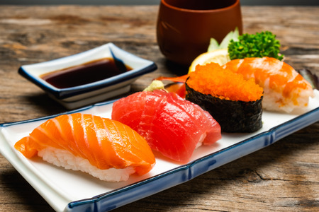 Sushi salmon & tuna sushi shrimp and wasabi on the white plate. on the wood table 免版税图像