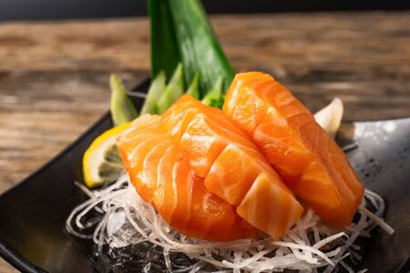 Sashimi, Salmon, Japanese food chopsticks and wasabi on the wood table 免版税图像 - 133684806