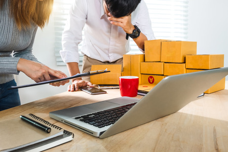 young Asian man and woman at office of their business online shopping.In home office 免版税图像