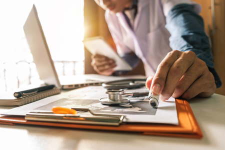 Medical technology concept. Doctor working with mobile phone and stethoscope and digital tablet laptop in modern office at hospital in morning light