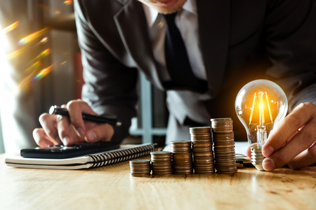 business man hand holding lightbulb with using smartphone and calculator to calculate and money stack. idea saving energy and accounting finance in morning light 免版税图像