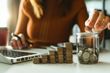 businessman holding coins putting in glass with using smartphone and calculator to calculate  concept saving money for finance accounting 免版税图像 - 116566347