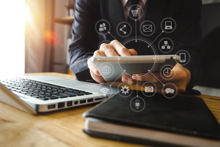 Businesswoman hand working digital marketing media in virtual screen with mobile phone and modern compute with VR icon diagram at office in morning light 免版税图像 - 116566018
