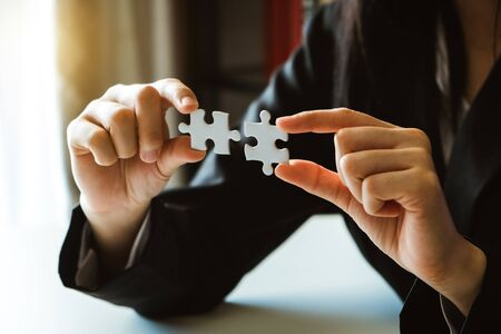 Business solutions and success concept. Businessman hand connecting jigsaw puzzle.