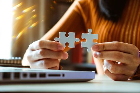 Business solutions and success concept. Businessman hand connecting jigsaw puzzle at office in morning light 免版税图像