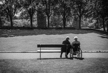 mujeres mayores: Amar par mayor activo se relaja en banco de madera en el parque en un día soleado de verano