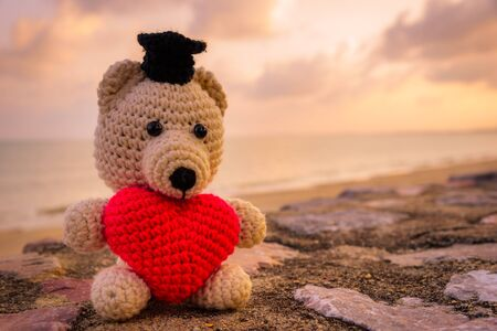 teddy bear love: Teddy Bear with red heart sitting near the beach - vintage tone