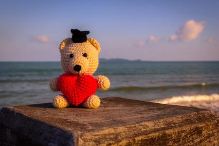 sand toys: Teddy Bear with red heart sitting near the beach - vintage tone