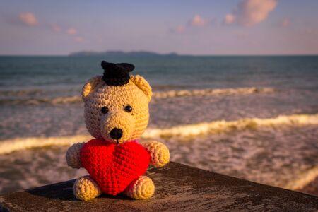 heart tone: Teddy Bear with red heart sitting near the beach - vintage tone