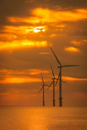Sunset Offshore Wind Turbine in a Wind farm under construction off the England coast Stock Photo