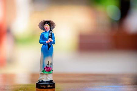 asean: Vietnam doll souvenir on wooden table with blurred background.