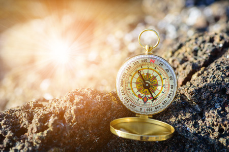 analogical: Analogical compass abandoned on the rocks with blurred sea background. Stock Photo