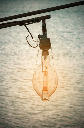 Lamp for fishing boat on sunset with blurred sea background. Stock Photo