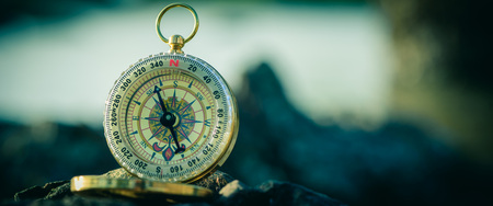 analogical: Analogical compass abandoned on the rocks with blurred sea background. Cinematic Style