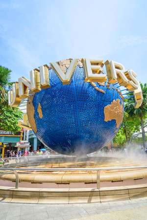 SINGAPORE - JULY 9: Tourists and theme park visitors taking pictures of the large rotating globe fountain in front of Universal Studios on JULY 9, 2014 in Sentosa island, Singapore