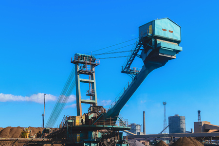 trencher: Loading iron ore conveyor machine in steel industry, UK
