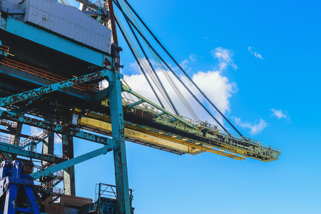 Cargo cranes in jetty over blue sky background. Stock Photo