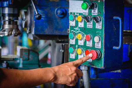 Finger push on red emergency stop switch milling machine in factory workshop. Stock Photo - 62946687