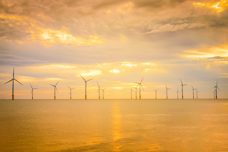 Sunset Offshore Wind Turbine in a Wind farm under construction off coast of England. Stock Photo