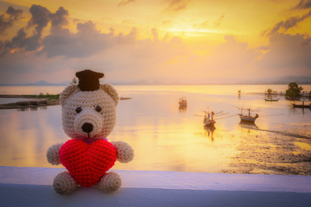 Teddy Bear with red heart sitting near the beach - vintage tone