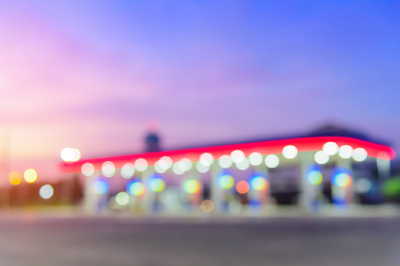 Blurred image of gas station with bokeh background at sunset