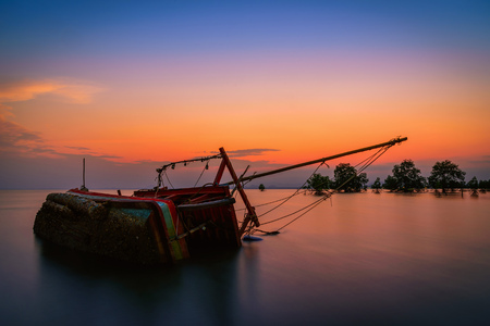 The old fishing boat capsized on sea at sunset in Phuket, Thailand.