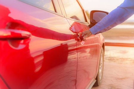 keyless: Close up woman hand opening red car door. Stock Photo