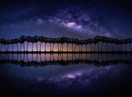 밀키 웨이 은하계 풍경. 밤 하늘에 별과 실루엣 코코넛 야자수 해변입니다. 긴 노출 사진입니다.