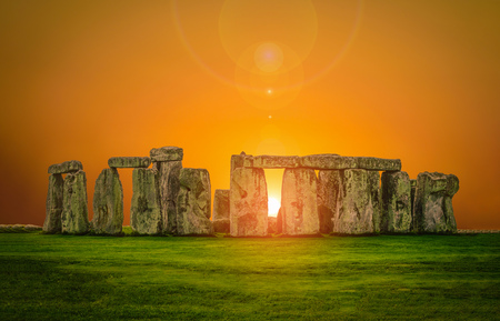 Stonehenge an ancient prehistoric stone monument at sunset with len flare in Wiltshire, UK.