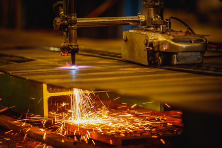 Worker cutting steel plate with acetylene welding cutting torch and bright sparks in factory Stock Photo