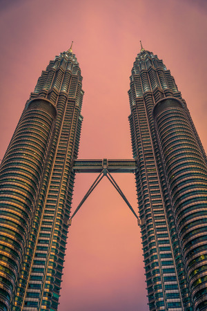 tallest bridge: KUALA LUMPUR, MALAYSIA - JULY 29, 2017. Petronas Twin Towers skyscraper at sunset on July 29, 2017. The tallest buildings in the world from 1998 to 2004 and remain the tallest twin towers in the world. The buildings are a landmark of Kuala Lumpur